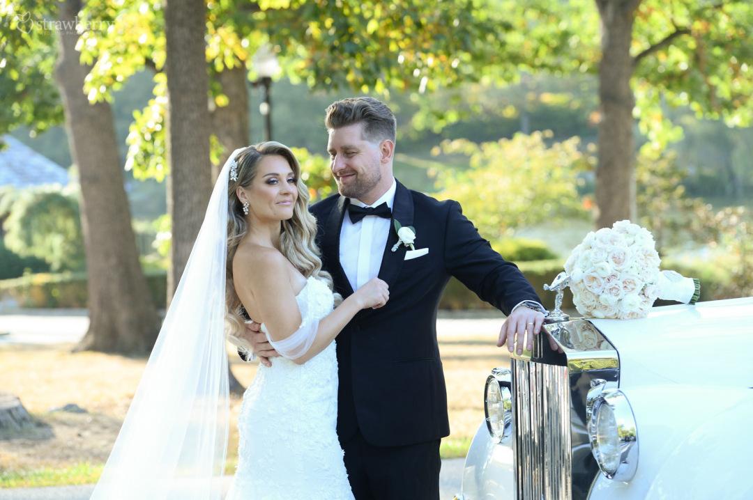 newlyweds-together-smile-wedding-bouquet-long-veil-car.jpg