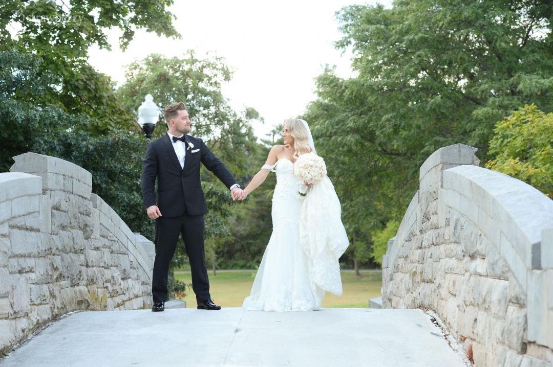 newlyweds-walk-park-romantic-scenery-brick-bridge.jpg