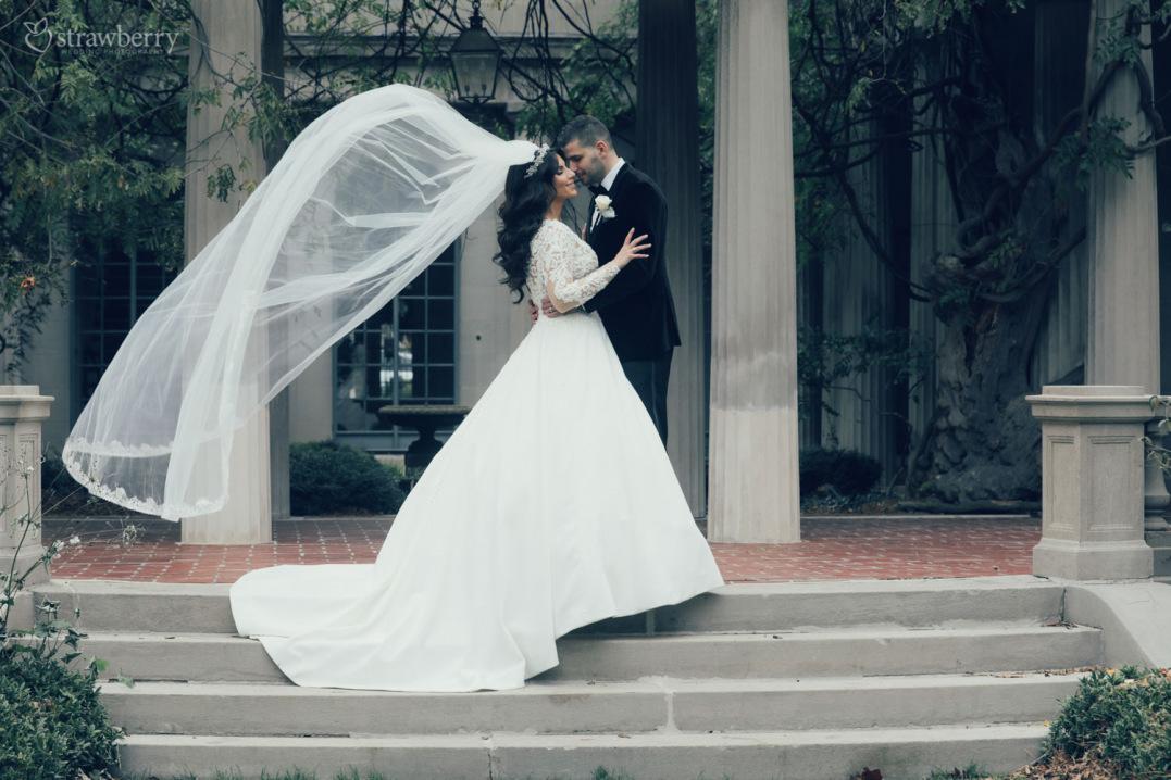 wedding-couple-standing-stairs-veil-kiss-1