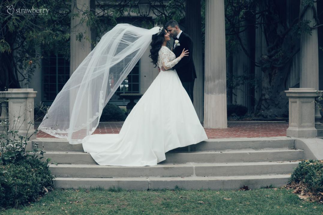 wedding-couple-standing-stairs-veil-kiss-2