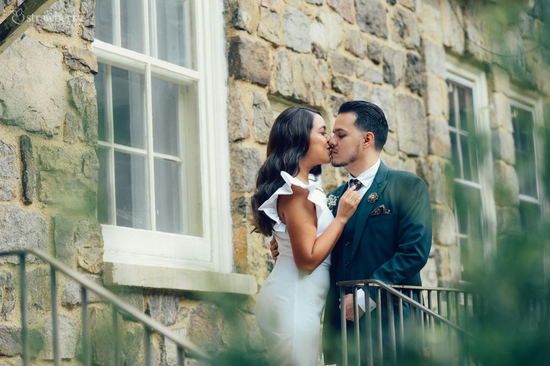 bride-groom-kissing-together-window-suit
