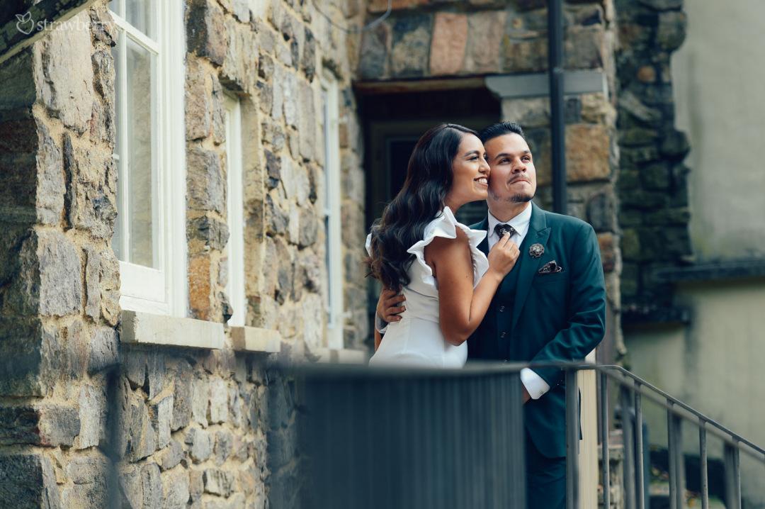 scenery-window-smile-embracing-bride-groom